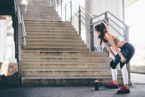 sporty woman looking at a big set of stairs